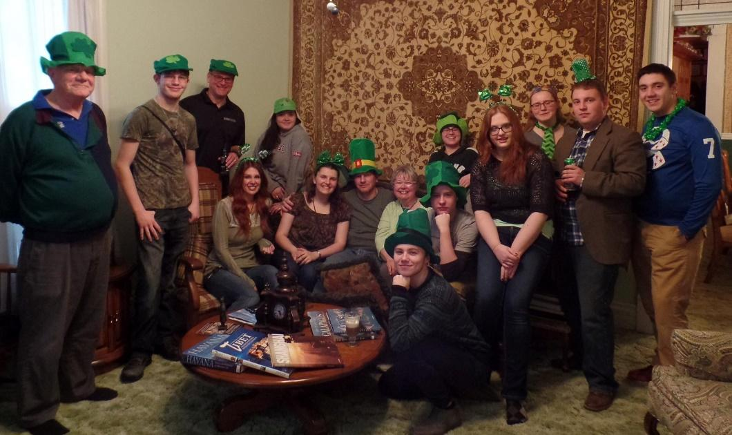 A group of people sitting around a table wearing green hats.