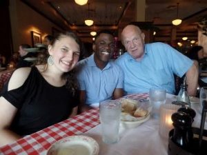 A young man, a young woman and an older man sitting at a restaurant table, smiling into the camera.