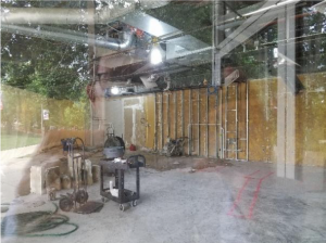 The insides of a coffee shop under construction is visible, as is the author's reflection in the glass.