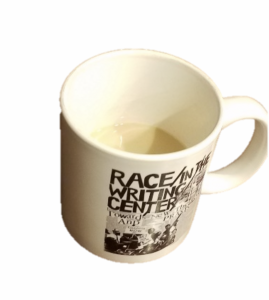 The picture is of a coffee mug with coffee inside. The mug is from a conference on Race and Writing Centers.