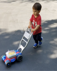 The author's youngest son pushes his bubble mower northwest across a driveway.