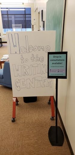 """Writing Center entryway. Small sign on the right and in the foreground reads, """"Drop in consultations available!"""" Larger sign to the left and in the background reads, """"Welcome to the Writing Center!"""""""