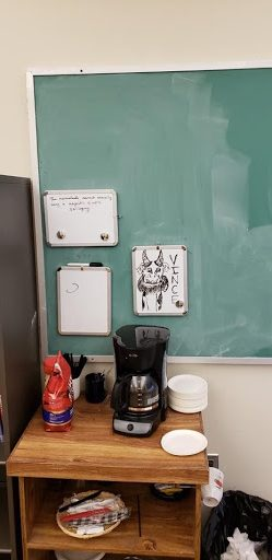 Coffee maker on a table in front of a green chalkboard.