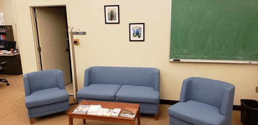 """UW Writing Center """"Lounge"""" Area: Two blue chairs, a blue loveseat, and a coffee table."""