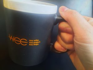 """Picture of hand holding a coffee mug, which has the words, """"WCC. Any writer. Any Project. Any Stage."""" written on it."""